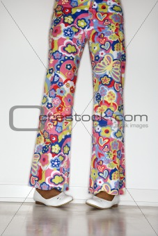 African-American teen girl's legs with floral pants and white sh