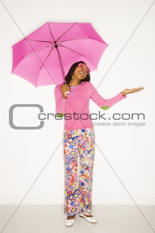 African-American teen girl holding pink umbrella.