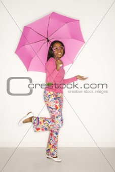 African-American teen girl holding a pink umbrella.