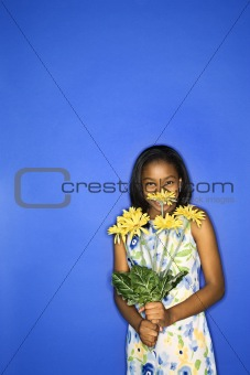 African-American teen girl holding daisies.