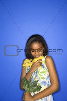 African-American teen girl smelling daisies.