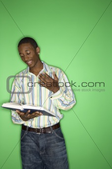 African-American teen boy reading book.