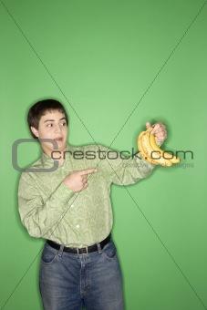 Caucasian teen boy pointing at bananas.
