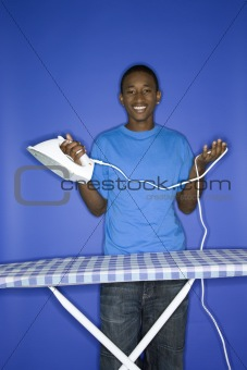 African-American teen boy doing ironing.