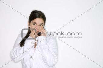 Caucasian teen girl whispering  into cellphone.