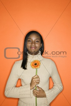 African-American teen girl holding daisy.