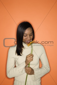 African-American teen girl smelling flower.