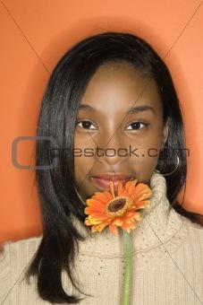 African-American teen girl holding flower.