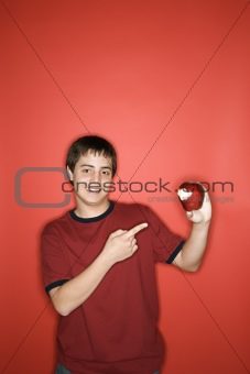 Caucasian teen boy pointing to apple.
