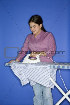 Caucasian teen girl ironing shirt.