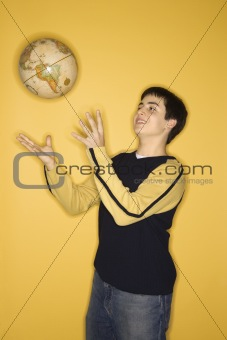 Caucasian teen boy tossing globe.