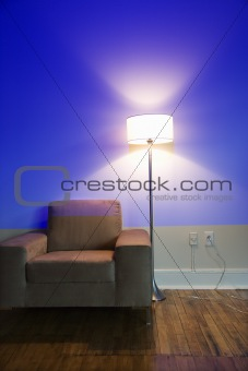 Chair and lamp against  blue wall.