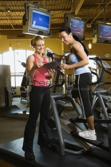 Adult female on elliptical machine with trainer.