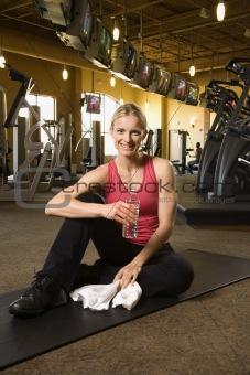 Adult female sitting on mat on gym floor.