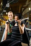 Adult female trainer helping adult female on exercise machine.