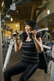 Adult female using exercise machine.