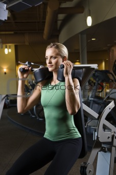 Adult female using exercise equipment at gym.