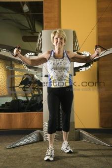 Adult female using exercise equipment.