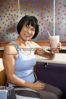 Adult female sitting at table in health club.