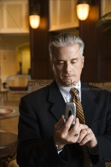 Businessman dialing cellphone in hotel lobby.