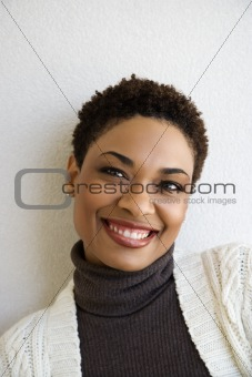 Adult woman standing against white wall smiling.