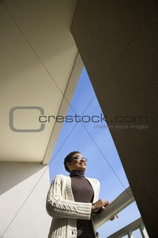 Adult woman leaning on rail looking out.