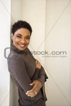 Adult woman leaning against wall smiling.