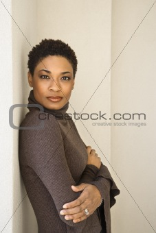 Adult woman leaning against wall.