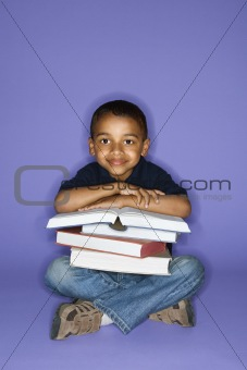Boy sitting with books.