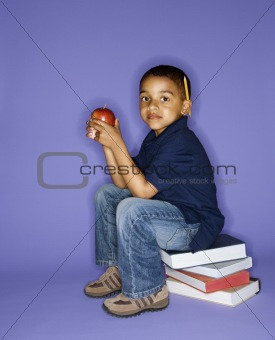 Boy sitting on stack of books.