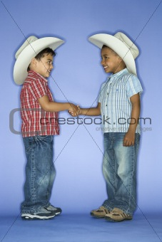 Boys in cowboy hats shaking hands.