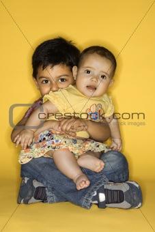 Boy holding baby female.