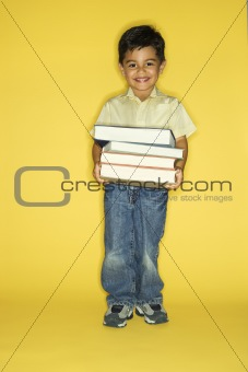 Boy holding stack of books.
