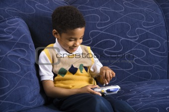 Young boy playing video game on couch.