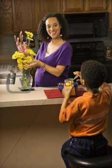 Pregnant mom arranging flowers while son eats breakfast.