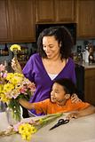 Pregnant mother and son arranging flowers.