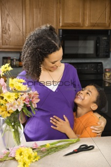 Pregnant mother and son in kitchen.