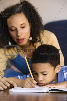 Portrait of mom helping son with homework.