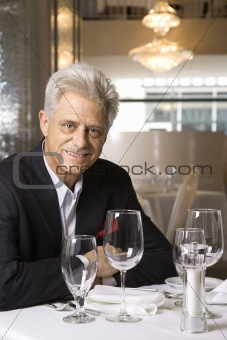 Adult male sitting at restaurant table.