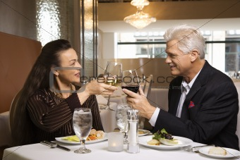 Adult male and female sitting at restaurant table toasting.