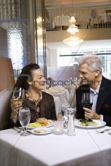 Adult male and female sitting at restaurant table.