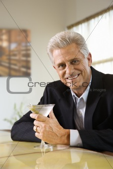 Adult male at bar with martini.