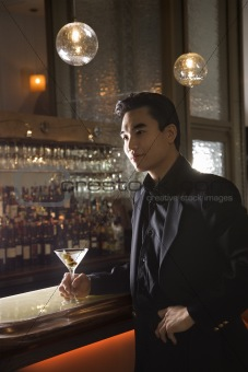 Adult male standing at bar with cocktail.