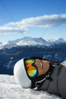 Boy snowboarder lying on mountain.