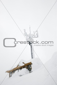 Cabin and antenna covered in snow.