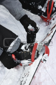 Person strapping on snowboard.