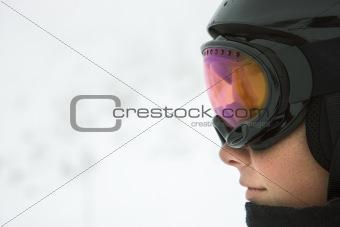 Boy skier wearing goggles and helmet.