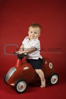 Baby boy sitting on play car.