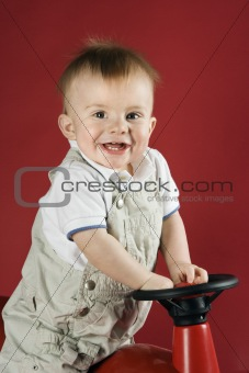 Baby boy driving play car.