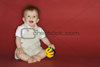 Baby boy playing with ball.